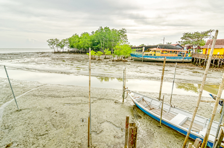 the major tide: Boat stranded on major routes at low tide when the weather is overcast and dark clouds Editorial
