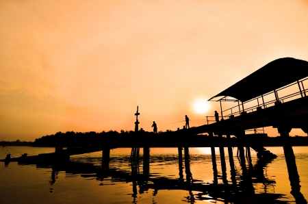 Silhouette man fishing at boat jetty photo
