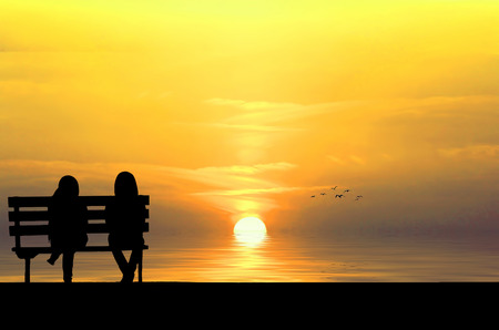 Silhouette of two friends sitting on wood bench near beach staring at flying bird photo