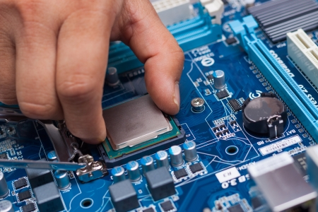 alto rendimiento: Montaje de alto rendimiento de PC, CPU insertar el procesador en el z�calo de la placa base, abri� caja de la PC en el fondo, profundidad de campo, se centran en la mano