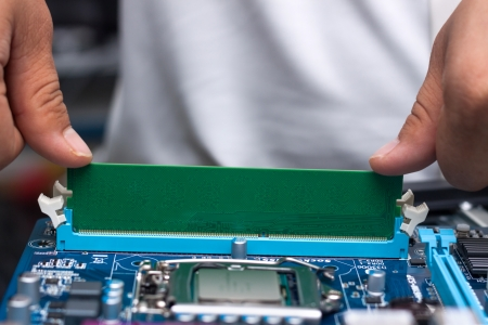 mainboard: Technicians hands installing user memory on a computer main-board Stock Photo