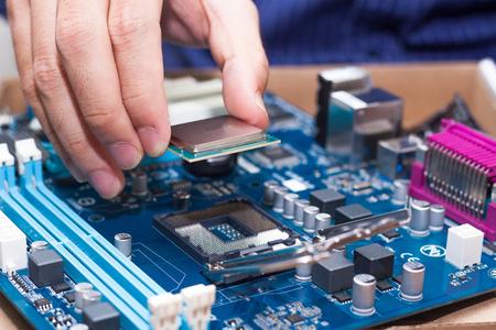 ensamblaje: Montaje de alto rendimiento de PC, CPU insertar el procesador en el zócalo de la placa base, abrió caja de la PC en el fondo, profundidad de campo, se centran en la mano