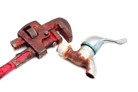 Dirty and rusty pipe wrench with taps photo