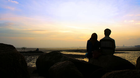 Silhouette of couple sitting on the rock looking at the sun goes down photo