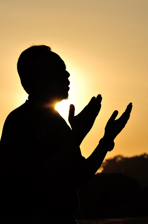 Silhouette of a Muslim praying over golden sunset photo