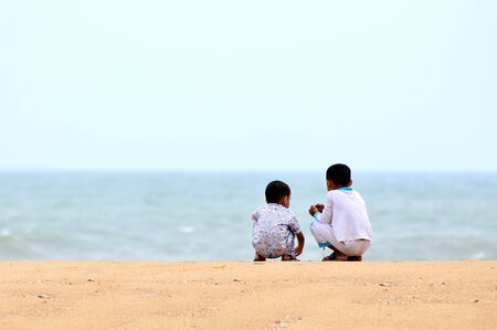 Two kids playing on the sand beach photo