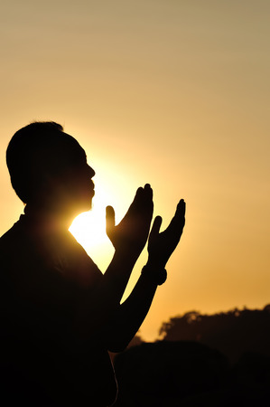 Silhouette of a Muslim praying over golden sunset Stock Photo