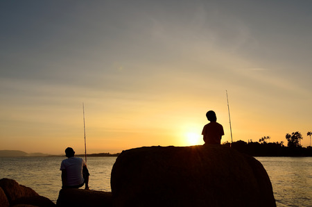 Silhouette of Father and son fishing in ocean surf at sunset. photo