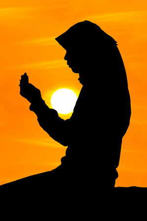 silhouettes of a women praying during sunset photo