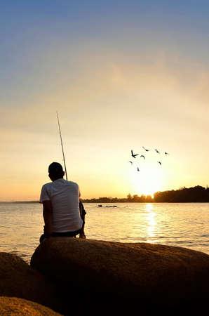 hombre pescando: Silueta del pescador en la playa al atardecer colorido Foto de archivo