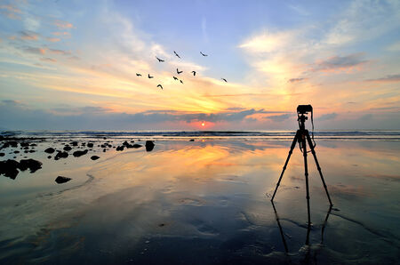 Camera with tripod over sun rising near the beach