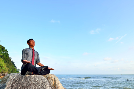 Businessman meditating on a rock. Soft Focus on man photo