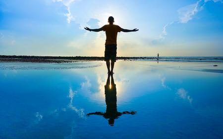 cielos abiertos: Silueta del hombre levant� las manos o los brazos abiertos cuando el sol se levanta Foto de archivo