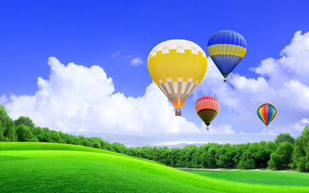 Hot air balloon floating in the sky over the hill Standard-Bild