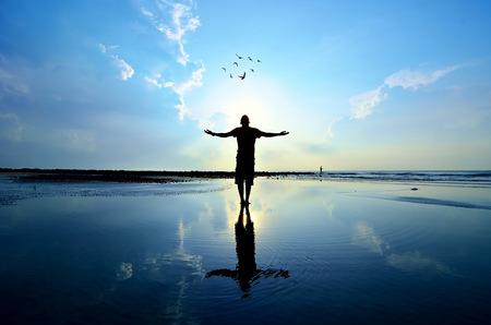 シルエットの男は、彼の手を上げるまたは開いている武器に昇る太陽