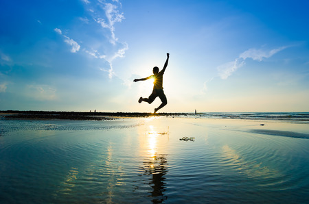 radost: Silueta muže, skákání přes slunce stoupá vzhůru Reklamní fotografie