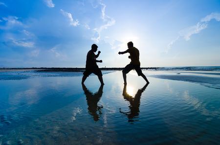 La lucha contra un enemigo cerca de la playa cuando el sol se levanta Foto de archivo - 28760252