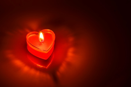 Close Up of burning red candle heart on dark  photo