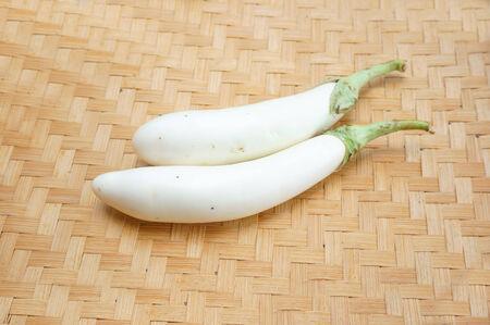 rattan mat: White eggplant or aubergine vegetables on rattan mat Stock Photo