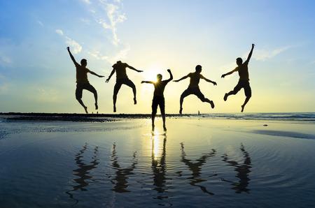 Silhouet van vrienden springen over zon oprijzen