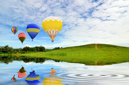 Hot air balloon floating in the sky over green grass photo