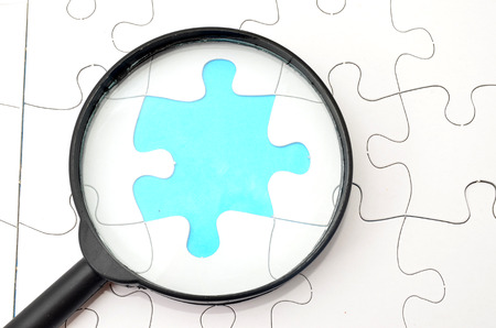 Magnifying glass searching missing puzzle peace photo