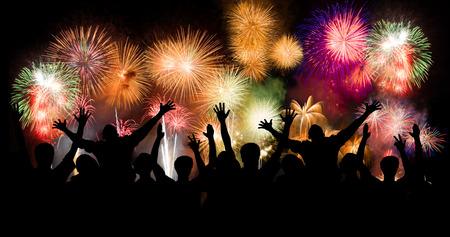 star bright: Grupo de personas disfrutando de los fuegos artificiales espectaculares muestran en un carnaval o vacaciones. La gente en silueta Foto de archivo