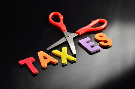 federal tax return: scissors and the alphabet TAXES Stock Photo