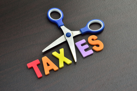 scissors and the alphabet TAXES Stock Photo