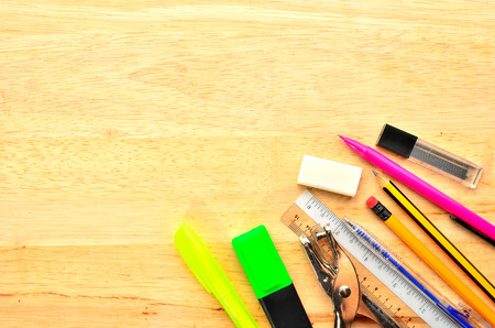 Assortment of various school items on wooden background photo