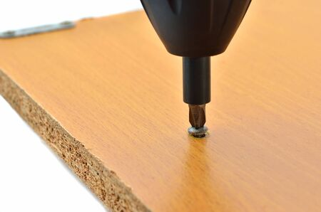 screwed: A screw being screwed into wood with a screwdriver