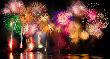 fireworks: Colorful fireworks. Fireworks are a class of explosive pyrotechnic devices used for aesthetic and entertainment purposes. Visible noise due to low light, soft focus, shallow DOF, slight motion blur Stock Photo