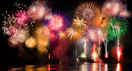 explode: Colorful fireworks. Fireworks are a class of explosive pyrotechnic devices used for aesthetic and entertainment purposes. Visible noise due to low light, soft focus, shallow DOF, slight motion blur Stock Photo