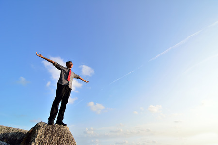 arms wide open: Man standing on the rock with his arms wide open