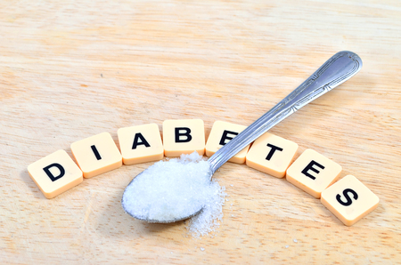 overuse: Diabetes word in crossword style block letters and spoon or teaspoon with white sugar in health care and healthy nutrition concept