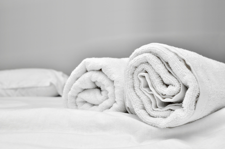 piled: Closeup of soft white towels, rolled and piled Stock Photo