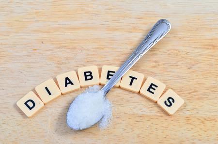 diabetes: Diabetes palabra en letras de imprenta estilo crucigrama y cuchara o cucharilla con azúcar blanco en el cuidado de la salud y el concepto de nutrición saludable