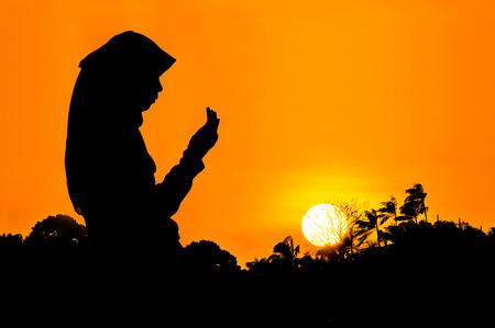 mujeres orando: siluetas de una mujer rezando durante la puesta de sol Foto de archivo