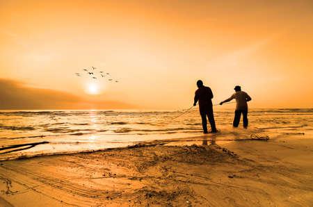 pescador: Los pescadores hacen su trabajo cerca de la playa
