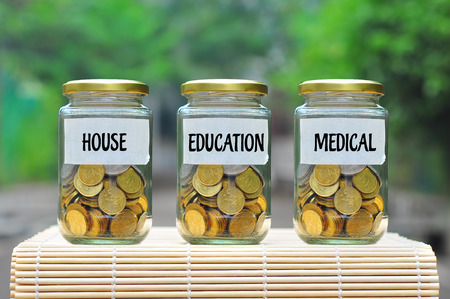 Coins in bottle with label House, Education and Medical - financial concept Archivio Fotografico