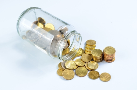 spilling: Coins spilling out of a glass bottle