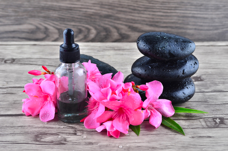 essence: Essence oil and flower with zen stone on wood background