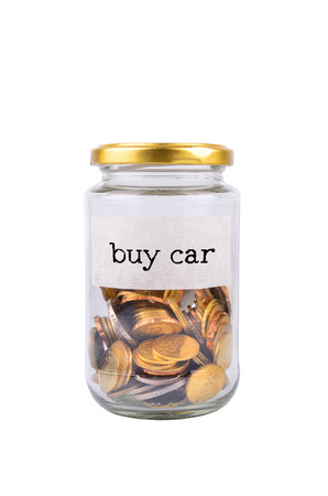 tax tips: Coins in bottle with label Buy Car isolated on white background - financial concept Stock Photo