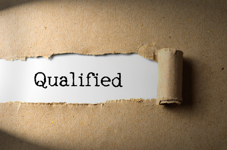 qualified worker: Torn paper with word Qualified
