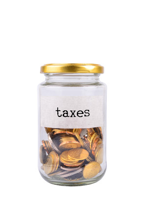 tax tips: Coins in bottle with label Taxes isolated on white background - financial concept