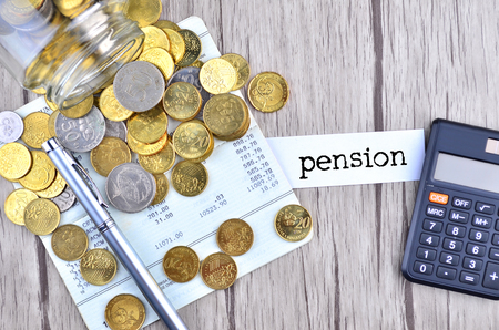 bank records: Coins, calculator and pen on bank account book with label pension
