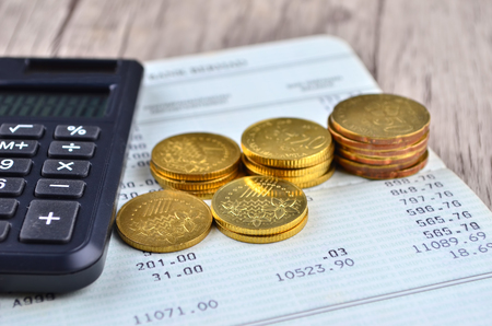 bank records: Coins, calculator and pen on bank account book Stock Photo