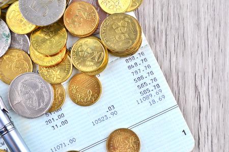 cuenta bancaria: Monedas con la pluma de plata en el libro de cuenta bancaria Foto de archivo