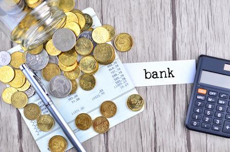 cuenta bancaria: Monedas, calculadora y pluma en el libro de cuenta bancaria con el banco de etiqueta
