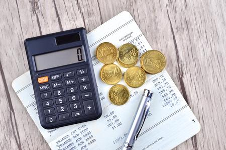 cuenta bancaria: Monedas, calculadora y pluma en el libro de cuenta bancaria